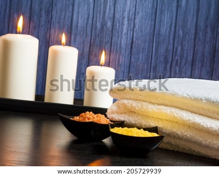 Spa massage border background with towel stacked,candles and sea salt on wood background - stock photo