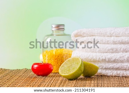 Spa massage border background with towel stacked,red candle and lime on green background - stock photo