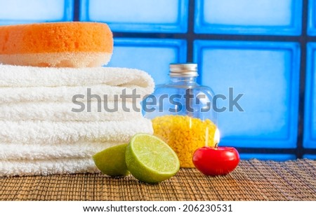 Spa massage border background with towel stacked red candle stone and lime on blue tiles background - stock photo