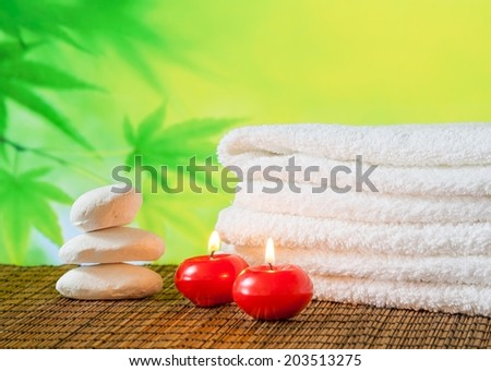 Spa massage border background with towel stacked,red candles and stone on green background - stock photo