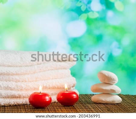 Spa massage border background with towel stacked,red candles and stone on green bokeh background - stock photo