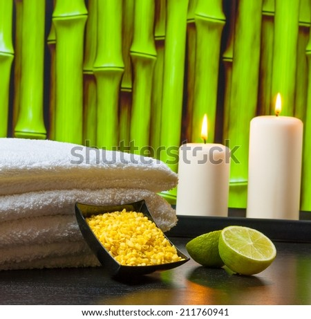 Spa massage border background with towel stacked sea salt candles and lime on green bamboo background - stock photo