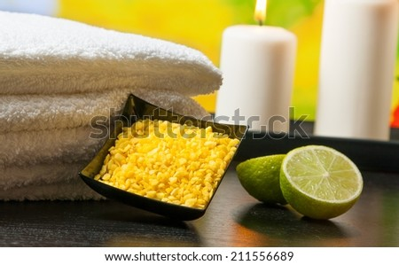 Spa massage border background with towel stacked sea salt candles and lime on green natural background - stock photo