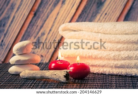 Spa massage border background with towel stacked stone and red candles on wood background - stock photo