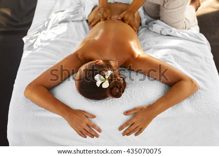 Spa Massage For Woman. Therapist Massaging Female Body With Aromatherapy Oil. Beautiful Healthy Happy Girl Relaxing Back Massage At Beauty Salon Outdoors. Skin Care Treatment, Health And Relaxation - stock photo