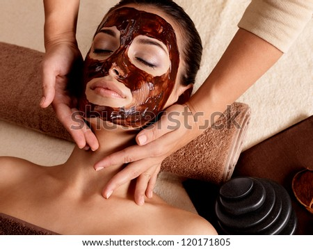 Spa massage for young woman with facial mask on face - indoors - stock photo