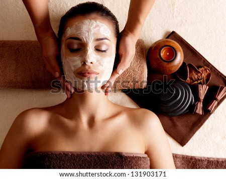 Spa massage for young woman with facial mask on face - indoors