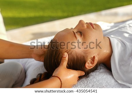 Spa Massage. Masseur Hand Massaging Girl's Head With Aromatherapy Oil. Closeup Of Beautiful Healthy Happy Woman Relaxing In Day Spa Salon Outdoors. Relax Beauty Body Care Treatment Concept - stock photo