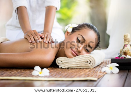 Spa massage outdoor, Balinese woman receiving back massage  - stock photo
