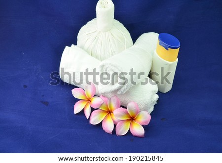 Spa massage setting with rolled towel, thai herbal compress balls and flowers - stock photo