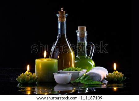Spa oil, candles  and spa cosmetics on black background - stock photo