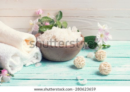 Spa or wellness setting. Sea salt in bowl, towels and apple blossom on turquoise wooden background against whit wall . Selective focus is on salt. Toned image.
