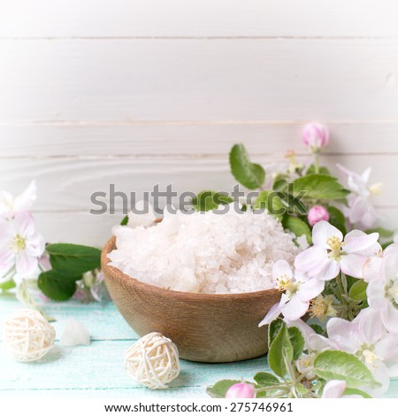 Spa or wellness setting. Sea salt in bowl with candle and apple blossom on turquoise wooden background against white wall. Selective focus is on salt. Square image.