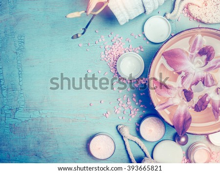 Spa or wellness setting with  cosmetic products , water bowl and orchid flowers on blue turquoise shabby chic background, top view, toned - stock photo