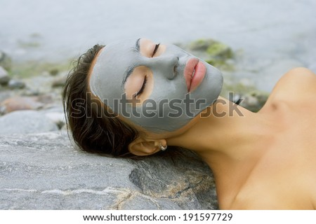 Spa Outdoor, Beautiful young woman lying with natural dead sea facial mask on her face. - stock photo