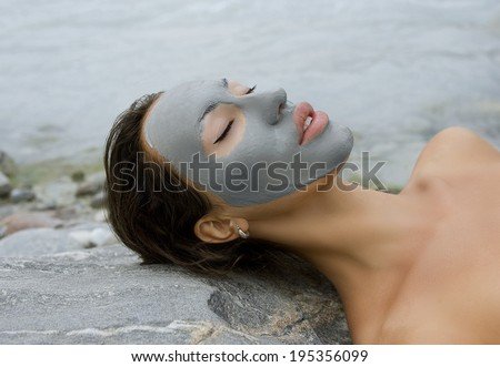 Spa Outdoor, Beautiful young woman lying with natural dead sea facial mask on her face - stock photo