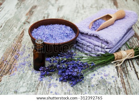 Spa products and lavender flowers on a wooden background - stock photo
