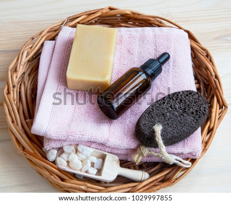 Spa products with natural soap , oil bottle and towel on a tray, body-care wellness products, home-spa concept