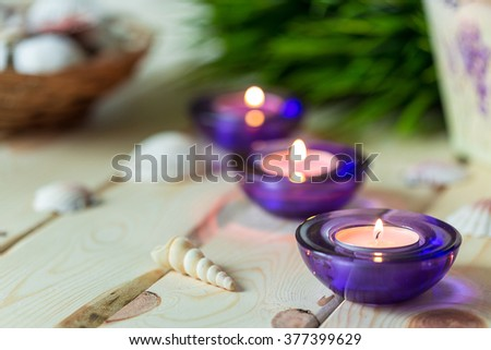 Spa Relax Set, Aromatic Candles in Purple Glass Candlesticks, Green Grass and Shells on Light Wooden Background, Close-up, Horizontal - stock photo