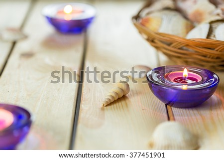 Spa Relax Set, Aromatic Candles in Purple Glass Candlesticks Shells on Light Wooden Background, Horizontal - stock photo