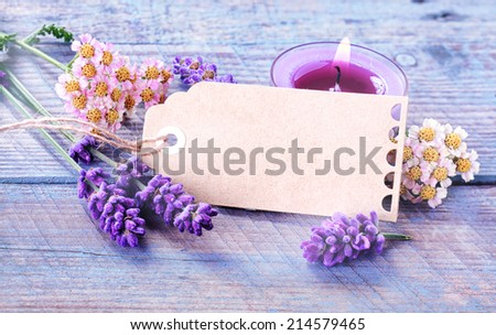 Spa, relaxation and wellness background with a blank gift tag or label with copyspace amongst fresh lavender and flowers with a burning candles for aromatherapy treatment on rustic blue wooden boards - stock photo