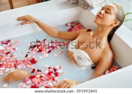 Spa Relaxation. Woman Body Care. Beautiful Sexy Caucasian Blonde Girl In Bikini Lying In Flower Bath In Resort Day Spa Salon. Beauty Treatment, Skin Care Therapy. Wellness. Healthy Lifestyle Concept - stock photo