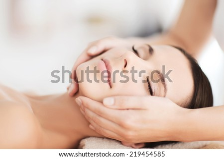 spa, resort, beauty and health concept - beautiful woman in spa salon getting face treatment - stock photo