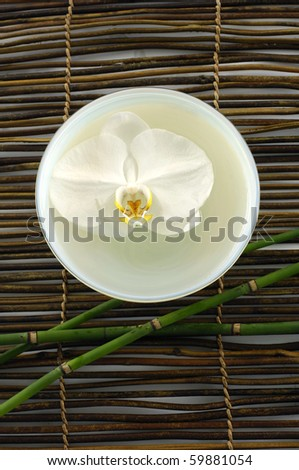 Spa resort composition-bowl of orchid and candle on mat
