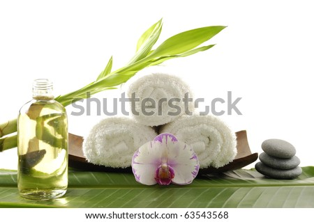 Spa resort composition- wooden bowl of towel with branch bamboo and massage oil on banana leaf - stock photo
