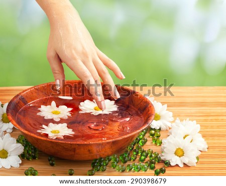 Spa Salon: Beautiful Female Hand with French Manicure in the Bamboo Bowl of Water with White and Yellow Flowers on the Straw Mat at the Nature Background  - stock photo