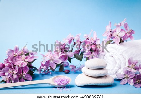Spa salt and stones, towel, flower branch for beauty and health. Healthy relaxation, therapy and treatment. Aromatherapy, body care, aroma massage. Alternative lifestyle. Relax in bath. - stock photo