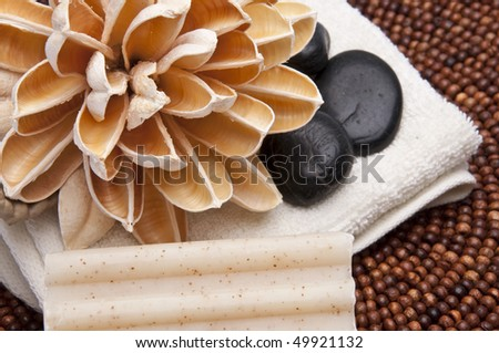 Spa scene with paper lotus flower, massage stones, towel and textured soap. - stock photo