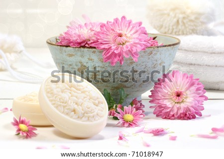 Spa scene with pink chrysanthemum flowers in water and soap - stock photo