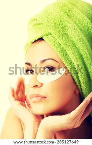 Spa serene woman with gel eye mask and hands on chin - stock photo