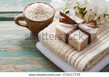Spa set: bar of handmade natural soap lying on the towels, cup of sea salt and alstroemeria flowers - stock photo