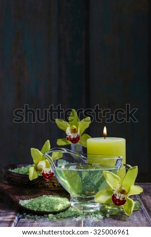 Spa set: liquid soap, sea salt on wooden spoon, scented candles. Black background, copy space.