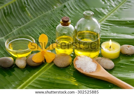 Spa set on banana leaf with pile of salt in spoon ,many oil