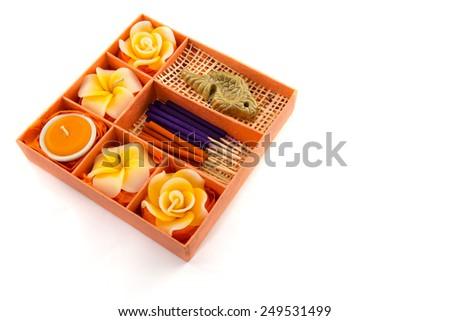 Spa Set. Roses Shaped Candles, incense sticks in orange box on white background - stock photo