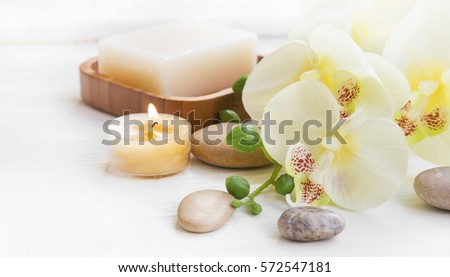 Spa set with orchid flower, candle, bath soap and massage stones