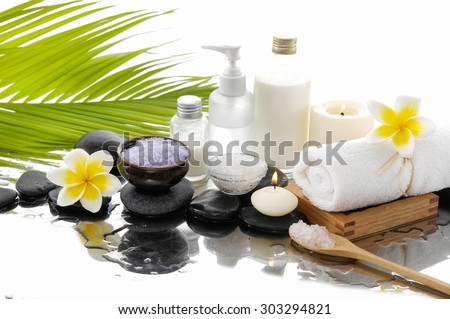 Spa set with salt in spoon, towel, candle ,oil, ,stones �green palm background - stock photo