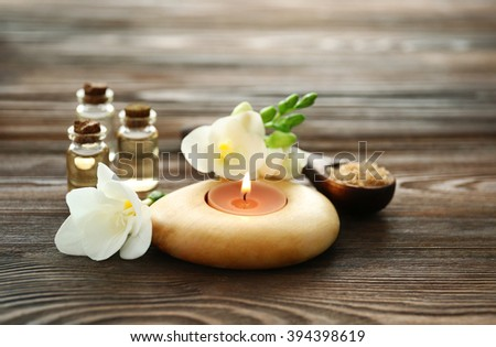 Spa set with sea salt, flowers and candles on wooden background