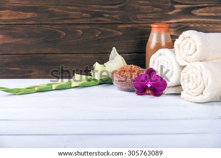 Spa sets with towels, scrubs and sea salt with orchid in the center at the white wooden table and brown wooden background. With copy space. - stock photo