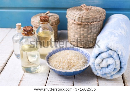 Spa setting. Bottles with essential aroma oil, sea salt in bowl  on  white wooden background against blue wall. Selective focus is on sea salt. - stock photo