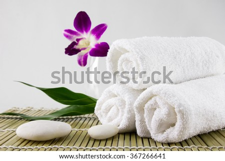 Spa setting decorated with green leave towel  and white stone. - stock photo