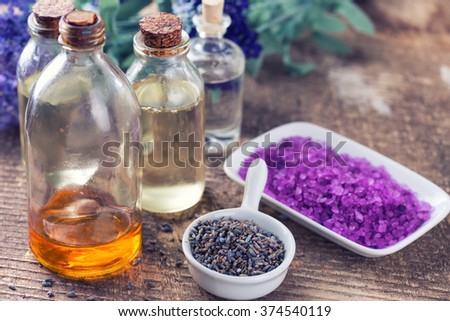 Spa setting. Dried lavender flowers, essential aroma oil with lavender, sea salt  on wooden background. Selective focus is on lavender flowers. - stock photo