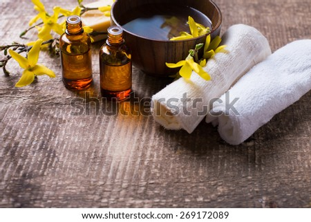 Spa setting. Essential aroma oil , water in bowl, towels, yellow flowers on aged wooden background. Selective focus. Place for text. - stock photo