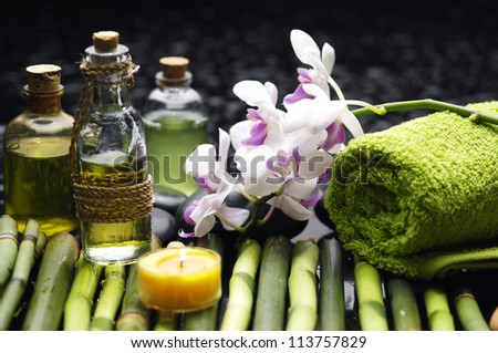 Spa setting green towel and massage oil ,candles on grove - stock photo