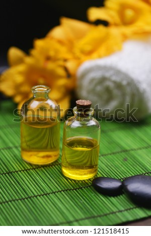 Spa setting �massage oil ,towel, stones, branch orchid