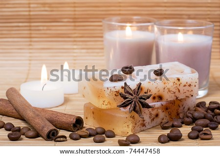 Spa setting: natural hand-made soap, cinnamon, coffee beans and candles - stock photo