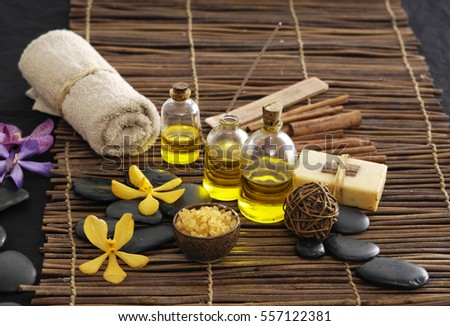 spa setting on brown background with yellow orchid, towel